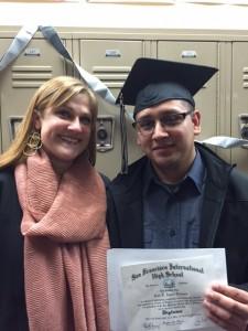 Juan Fernando shows off his graduation diploma with Julie Kessler, Principal.